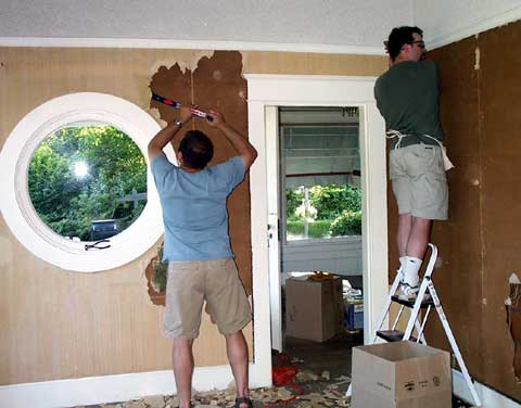 [Jeremy and J.D. remove wallboard]