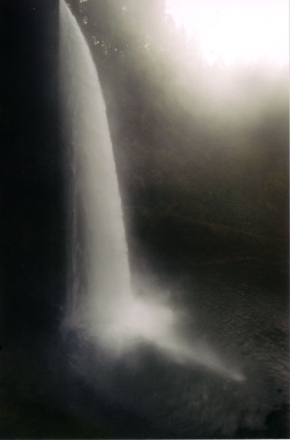 [Long, tall photograph of South Falls in which the falls is white against a black background]